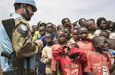 """Congolese children gather near a United Nations peacekeeper during the global rally """"One Billion Rising"""" which is part of a V-Day event calling for an end to gender-based violence, in Bukavu"""