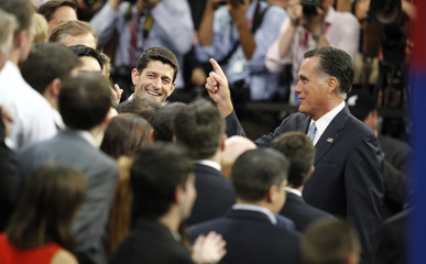 Republican vice presidential nominee Ryan and presidenial nominee Romney talk with members of their staff as they arrive in the convention hall during a walkthrough before the final session of the 2012 Republican National Convention in Tampa