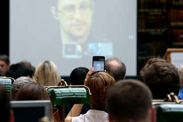 A participant takes a picture of Edward Snowden speaking via video link during the Athens Democracy Forum, organised by the New York Times, at the National Library in Athens