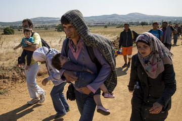 Migrants from Syria walk along a road in the village of Miratovac near the town of Presevo, Serbia