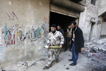 A Free Syrian Army fighter carries a mortar as he walks in Aleppo's Bustan al-Basha district