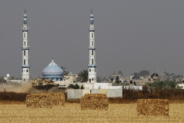 A mosque is seen in the background as an Israeli military tank manoeuvres along the border with the Gaza Strip, near Kibbutz Nirim