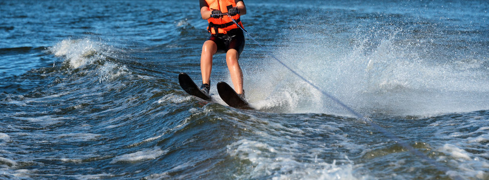 Woman riding water skis closeup. Body parts without a face. Athlete water skiing and having fun. Living a healthy lifestyle and staying active. Water sports theme. Summer by the sea. Banner for