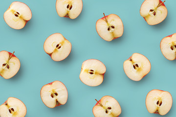 Apple slices pattern on a blue background. Repetition concept. Top view. Flat lay
