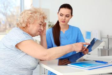 Female orthopedist examining senior woman in clinic
