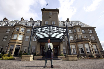 Linkman Duncan Hunter, who greets guests on arrival, poses for a photograph outside the Gleneagles Hotel in Perthshire, Scotland