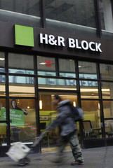 A man walks past the office of tax preparation company H&R Block, in New York