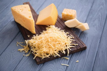 Wooden board with grated cheese on table