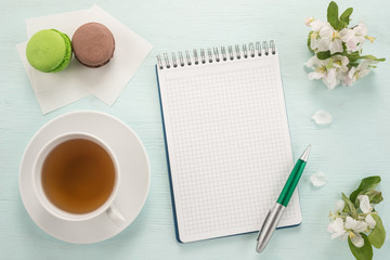 Notepad, pen, flowers, and macarons with cup of tea