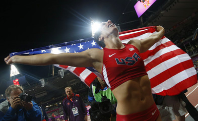 Jennifer Suhr of the U.S. holds her national flag after winning the women's pole vault final at the London 2012 Olympic Games