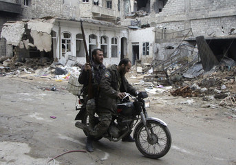 Free Syrian Army fighters ride a motorcycle along a street in Aleppo