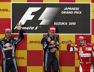 Winner Red Bull driver Vettel, second placed team mate Webber and third placed Ferrari driver Alonso celebrate on podium at the Suzuka circuit