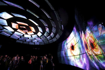 Attendees watch a display of 4K OLED televisions at the LG Electronics booth during the 2016 CES trade show in Las Vegas