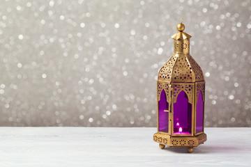Lightened lantern on wooden table over bokeh background. Ramadan kareem holiday celebration concept