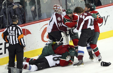 Colorado Avalanche Budaj holds back Minnesota Wild Cullen from teammate Wilson in St. Paul