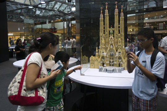 Visitors look at a miniature model of Spain's Basilica Sagrada Familia during the LEGO Piece of Peace-World Heritage Exhibition in Hong Kong