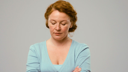 Mid aged actress showing emotions of sadness. Actress in studio shows the emotion of sadness. Close-up portrait of actrees in light blue jumper. Woman with curly red hair shows the emotion of sadness