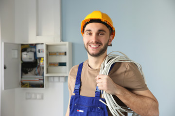 Young smiling electrician with bunch of wires indoors