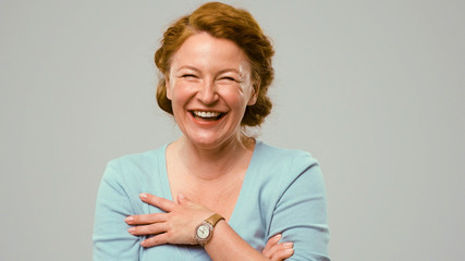 Mid aged woman showing emotions of happiness. Close-up portrait of an actrees in light blue jumper. Actress with curly red hair shows the emotion of happiness.