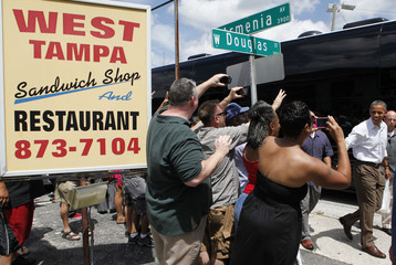 People take pictures of U.S. President Obama outside a sandwich shop in Tampa