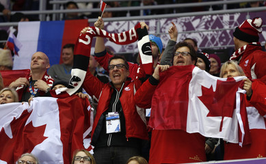 Fans of Team Canada cheer during the men's quarter-finals ice hockey game against Latvia at the 2014 Sochi Winter Olympic Games