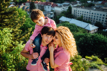 Portrait happy family of three. Father hugging mother and holding his son on the back. They standing and smiling on the hill with city view.