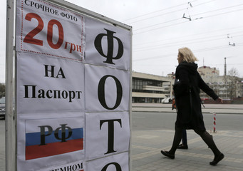People walk past an advertising board of a photo shop in the Crimean city of Simferopol