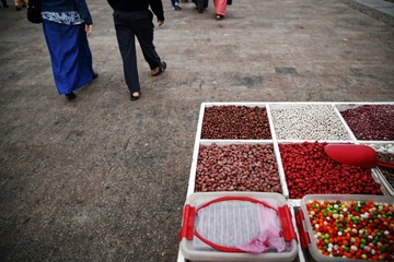 People stroll past peanuts, pumpkin seeds and other snacks offered for sale on a trolley in Rabat's Medina
