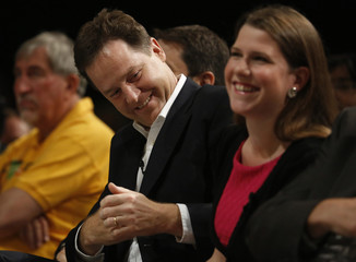 Britain's Deputy Prime Minister and leader of Liberal Democrat Party Clegg reacts during speeches as he sits next to MP Swinson in Brighton