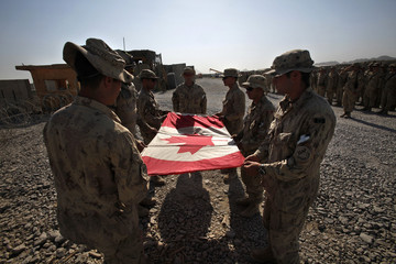 Canadian Army soldiers fold Canadian national flag during ceremony marking Canadian handover of forward fire base Zangabad to U.S. forces, in Panjwai district