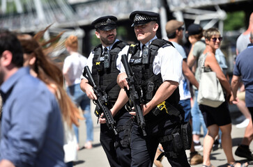 Armed police officers walk along the South Bank in London