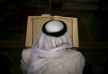 Palestinian man reads the Koran during the holy month of Ramadan at Al-Omari mosque in Gaza City