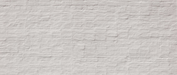 Whitewashed  painted wide old brick wall  with plaster texture. Background  for text or image.