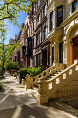 Row of brownstones with doorsteps and ornament in morning light. Upper West Side Street, Manhattan, New York City