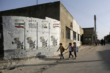 Children walk past a wall caricature depicting stages of the Syrian conflict since 2011 in the rebel-controlled area of Kafranbel