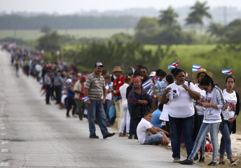 People line a road as they await the caravan carrying Fidel Castro's ashes in El Maja