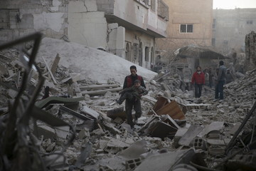 A man carries an injured boy amidst rubble in a site damaged from what activists said was shelling by forces loyal to Assad in the town of Douma