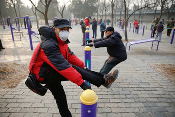 A man wearing a face mask exercises in a park despite a red alert issued for air pollution in Beijing