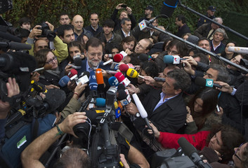 Spain's opposition centre-right People's Party leader Rajoy talks to reporters after casting his vote during a general election in Madrid