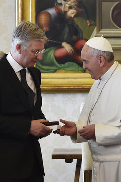 Pope Francis gives a gift to Belgium's King Philippe during a meeting at the Vatican