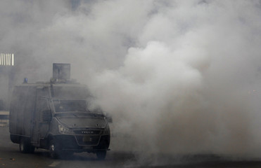 A police vehicle is surrounded by teargas fired by Egyptian security forces at Tahrir Square in Cairo