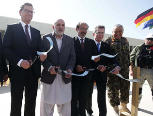 German Foreign Minister Westerwelle and Defence Minister De Maiziere cut a ribbon with Afghan officials during the handover ceremony of a German base to Afghan armed forces in Kunduz