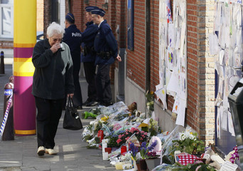 A woman, paying tribute to the victims of a bus crash in Switzerland, wipes her eyes while looking at flowers outside St Lambertus school in Heverlee