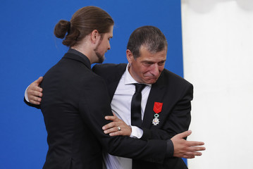Michel Catalano, the owner of the Dammartin print works, hugs Lilian Lepere, former employee and graphic designer, during the inauguration of the rebuilt groupe Michel Catalano printing house in Dammartin-en-Goele