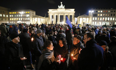People gather to mourn for the victims of the Charlie Hebdo shooting, in front of the Brandenburg Gate near the French embassy at Pariser Platz in Berlin