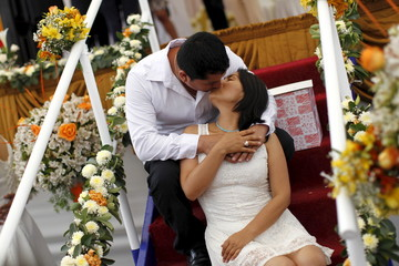 A couple kiss for a picture after a mass wedding ceremony ahead of Valentine's Day celebrations in Lima