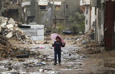 A Palestinian girl holds an umbrella as she walks past the ruins of a house that witnesses said was destroyed by Israeli shelling during the most recent conflict between Israel and Hamas, on a rainy day in the east of Gaza City
