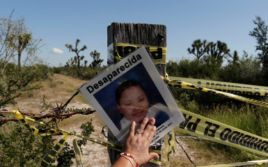 A picture of a missing woman is pictured during a mass with relatives of missing persons at the site where several bodies were found in mass graves in the municipality of Salinas Victoria Nuevo Leon Mexico