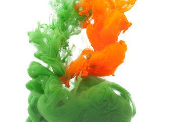 Colored green and orange clouds of paint in the water