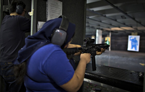 A woman fires a .22 calibre AR-15 rifle on the range at DVC Indoor Shooting Centre in Port Coquitlam, British Columbia